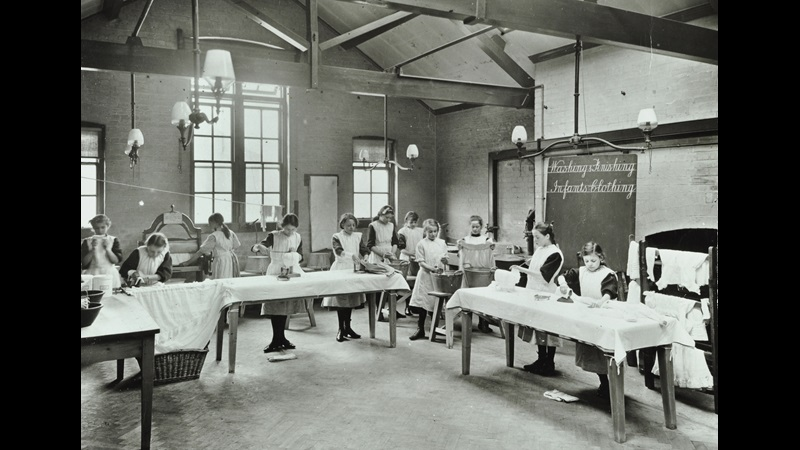 Photograph of a class of school girls learning to wash, iron and finish infants clothing at Beaufort House School in 1908. There are mangles, wash basins and steamers set on tables - the school children have pinafores over their uniforms.