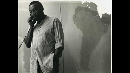 Frank Bowling in his New York studio loft, standing in front of South America x 3 at root 2 puce, 1967. Photo: Tina Tranter. Courtesy of Frank Bowling Archive. Image not licensed for reuse.