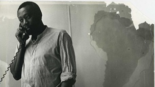 Frank Bowling in his New York studio loft, standing in front of South America x 3 at root 2 puce, 1967. Photo: Tina Tranter. Courtesy of Frank Bowling Archive.
