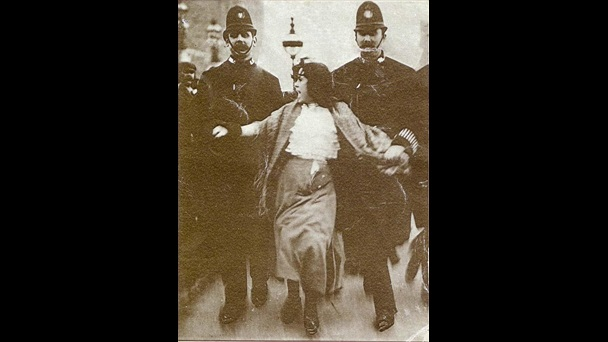 Photograph of Dora Thewlis being arrested by two police officers