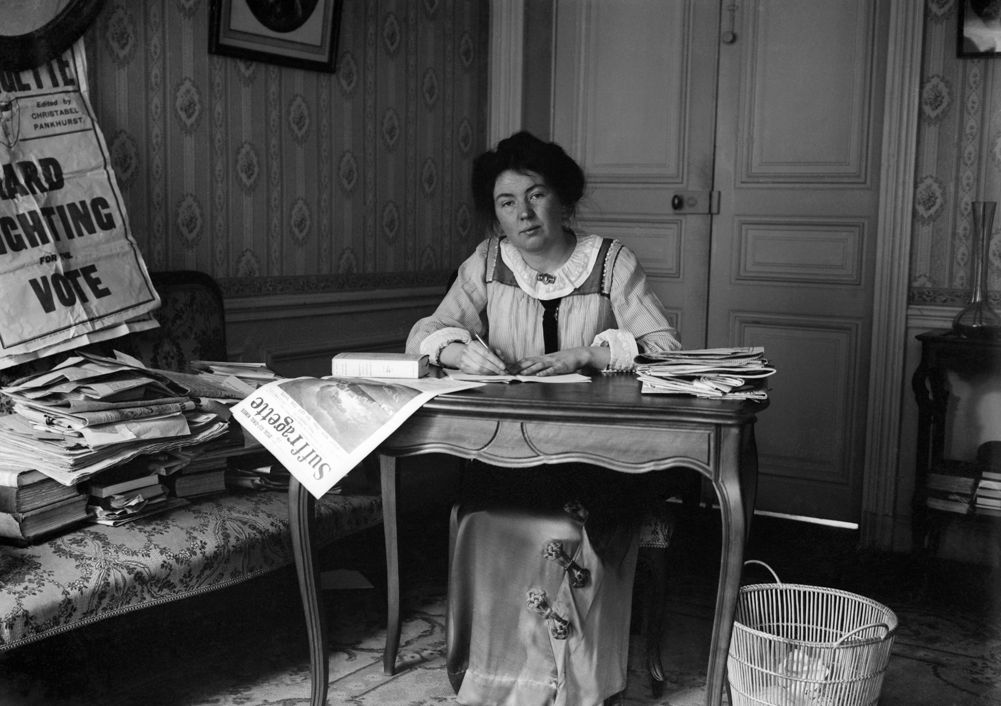 Photo of Christabel Pankhurst sitting at her desk with an isuse of The Suffragette newspaper hanging off the edge. To her left is a sofa with piles of books and demonstration materials