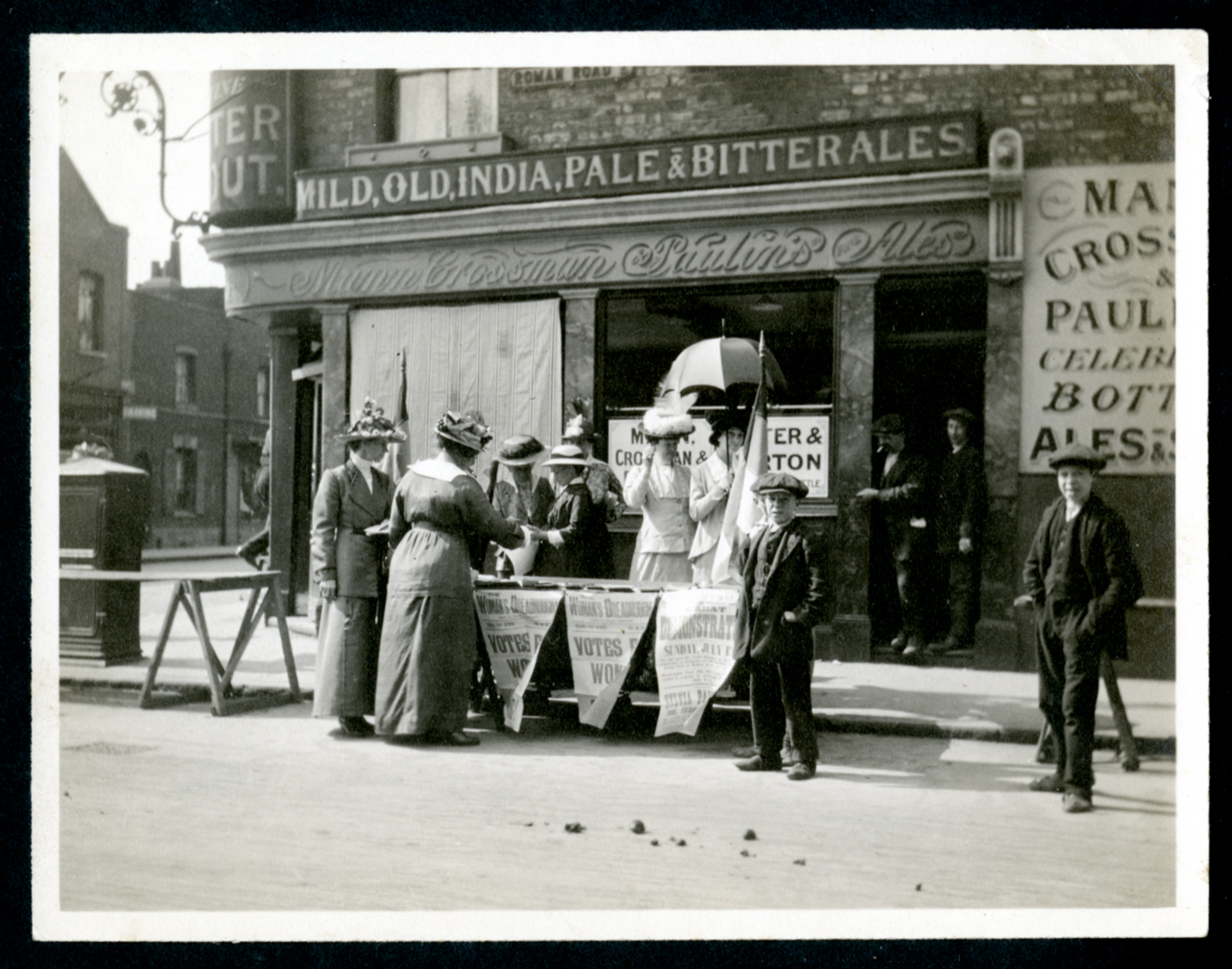 Stalls of the East London Federation of the Suffragetes in Roman Road with the announcement of the procession and meeting in Canning Town on July twelfth.