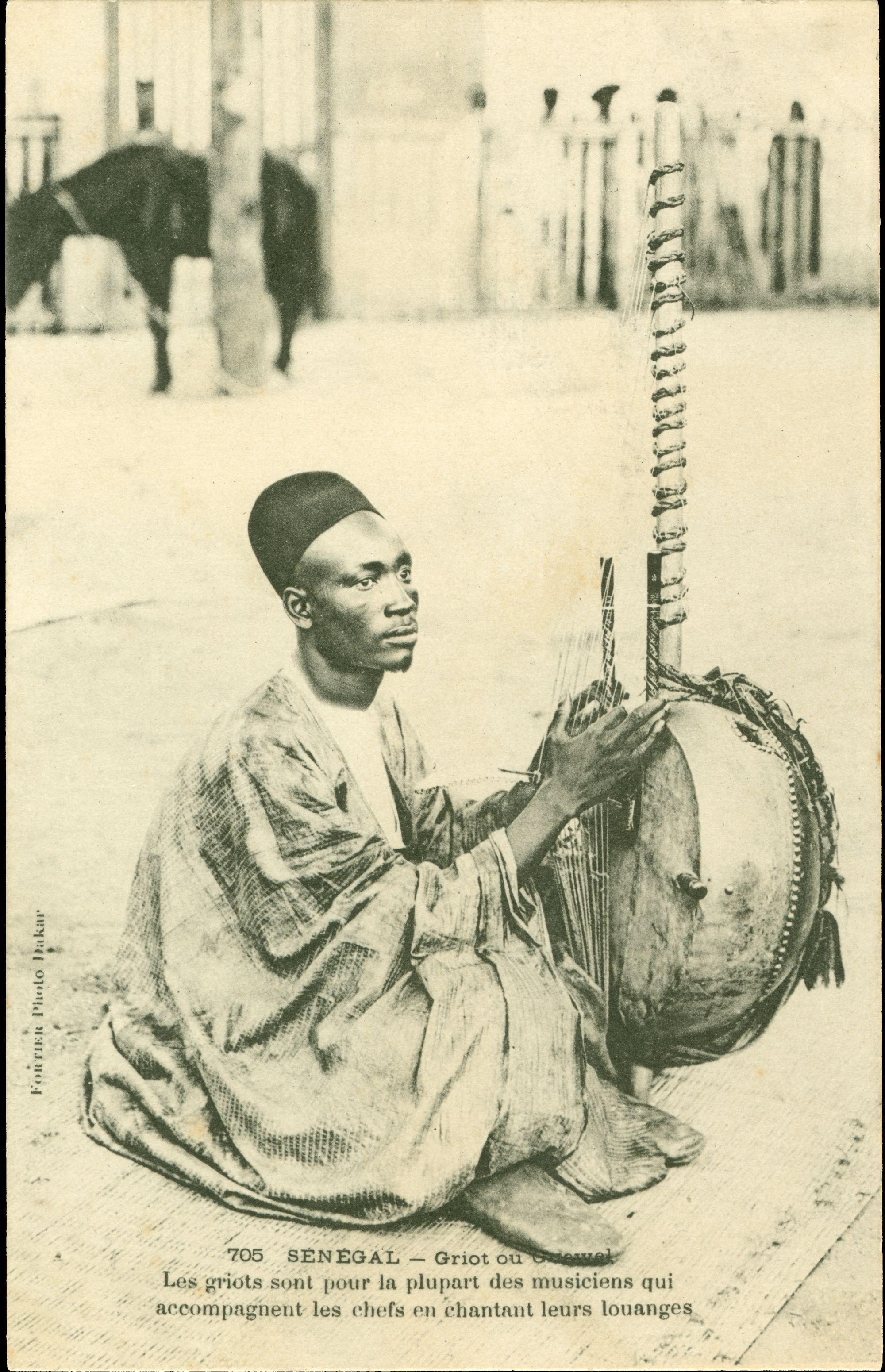 An image of a postcard showing a photograph of a griot, a story-teller or musician, playing his kora, a calbash harp.