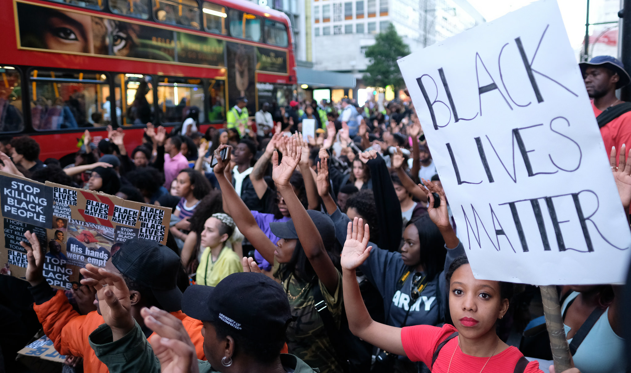 Black Lives Matter protesters in London's Oxford Street kneel and raise their hands, 8 July 2016. Photograph by Alisdare Hickson via Flickr