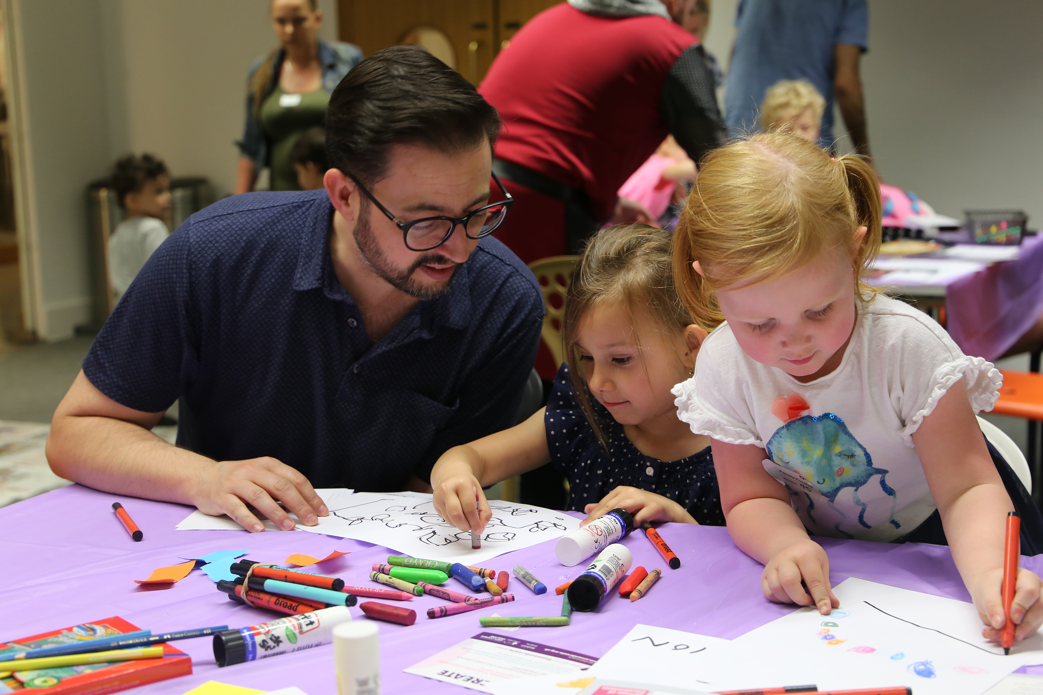 A man does art activities with his two children
