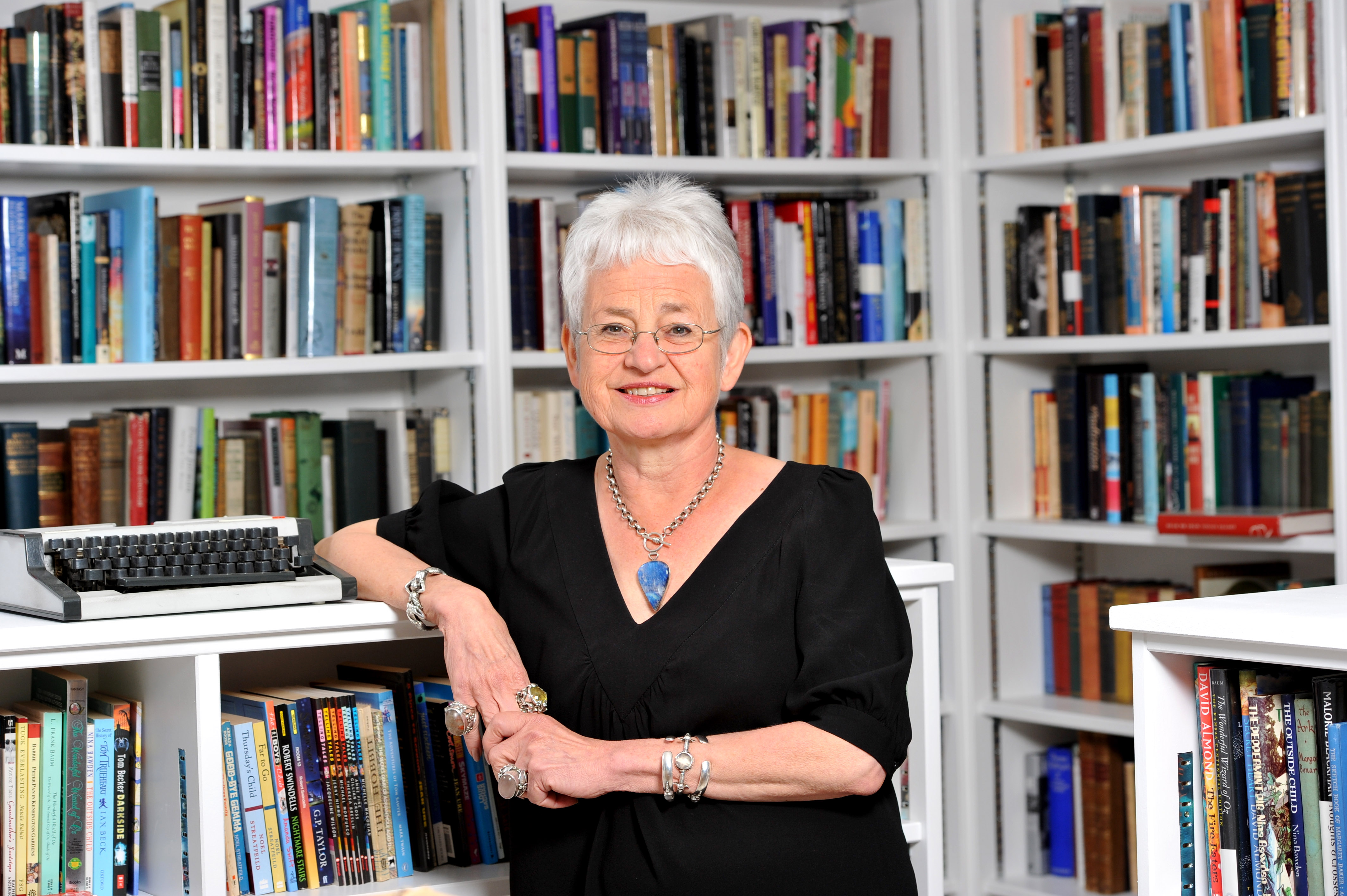 A photograph of Jacqueline Wilson standing next to a typewriter, surrounded by shelves of books