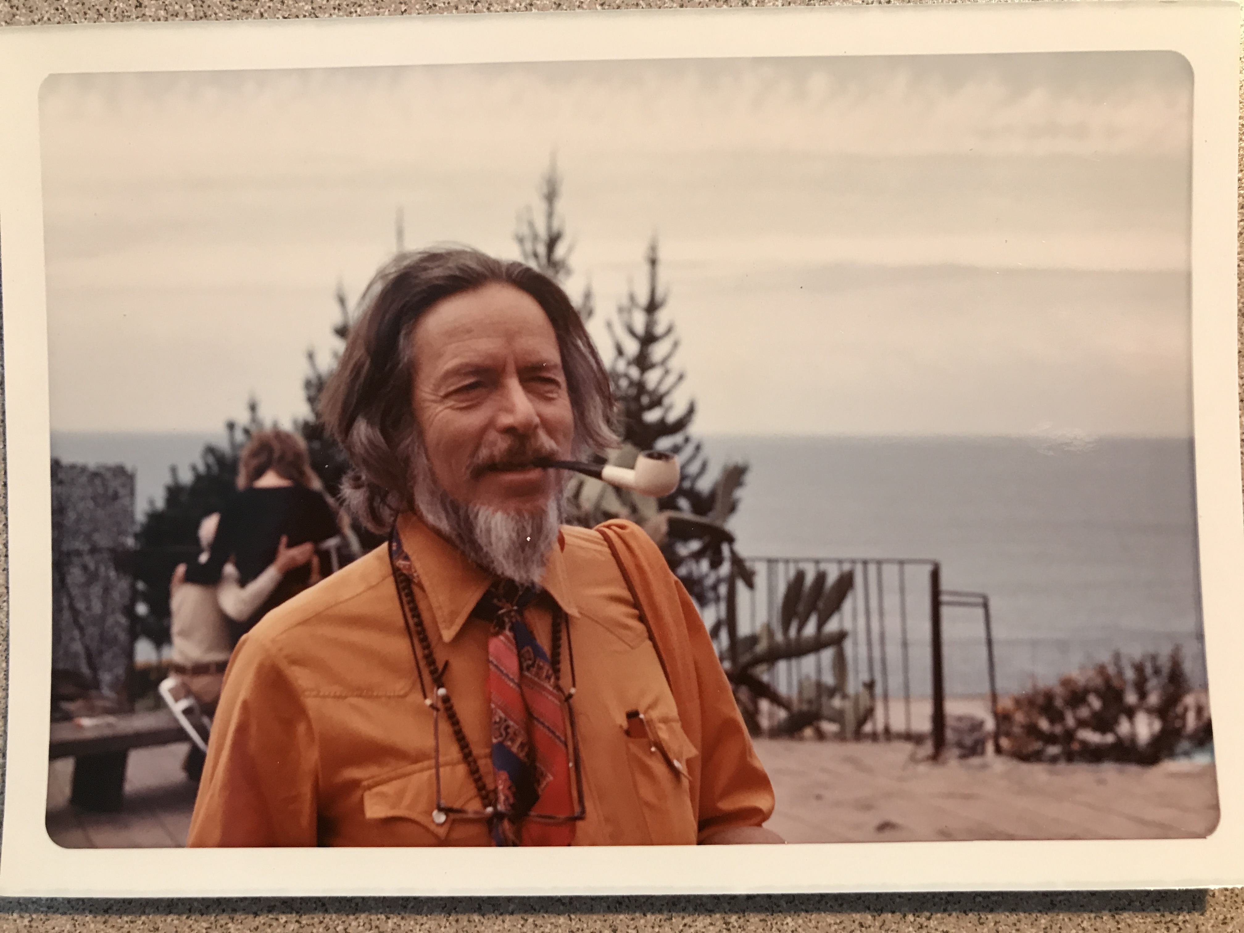 A photograph of Alan Watts smoking a pipe in Esalen, California in the 1960s or 70s