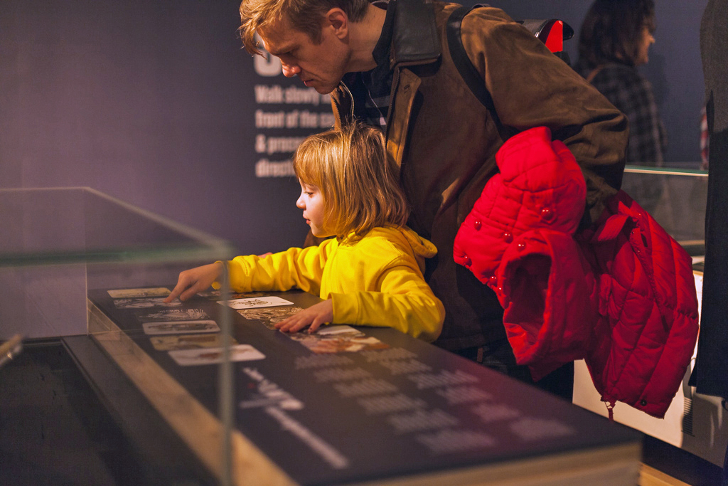 A girl in a yellow sweatshirt does an activity in an exhibition with her dad