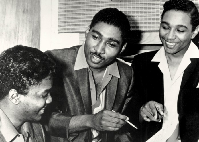 A black and white photograph of songwriters Brian Holland, Edward Holland and Lamont Dozier around a piano, smiling