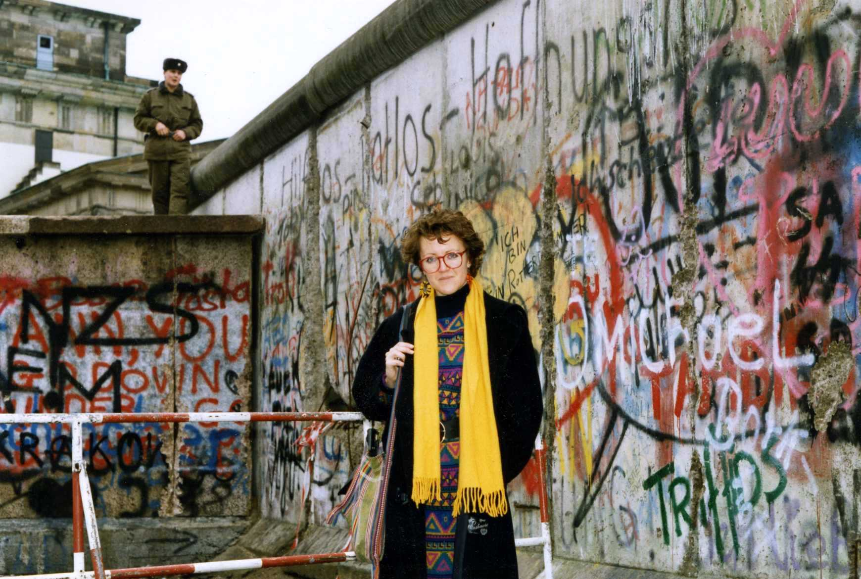 A photo of a woman in a yellow scarf standing in front of the Berlin Wall