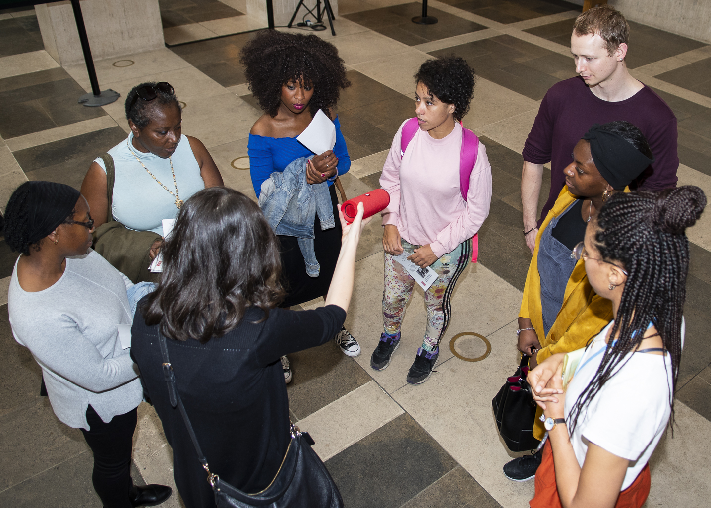 A tour group stand in a circle in the British Library Entrance Hall at St Pancras