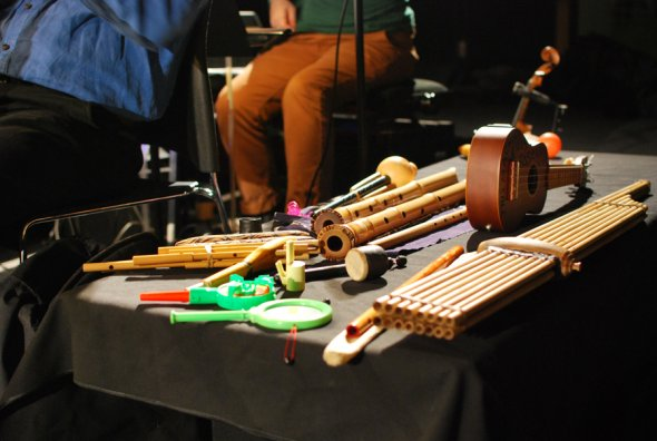 A photograph of wind, string and percussion instruments laid out on a table with performers nearby