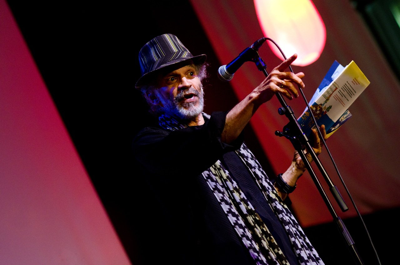 John Agard reads aloud from a book of poetry, standing at a microphone and pointing out at the audience