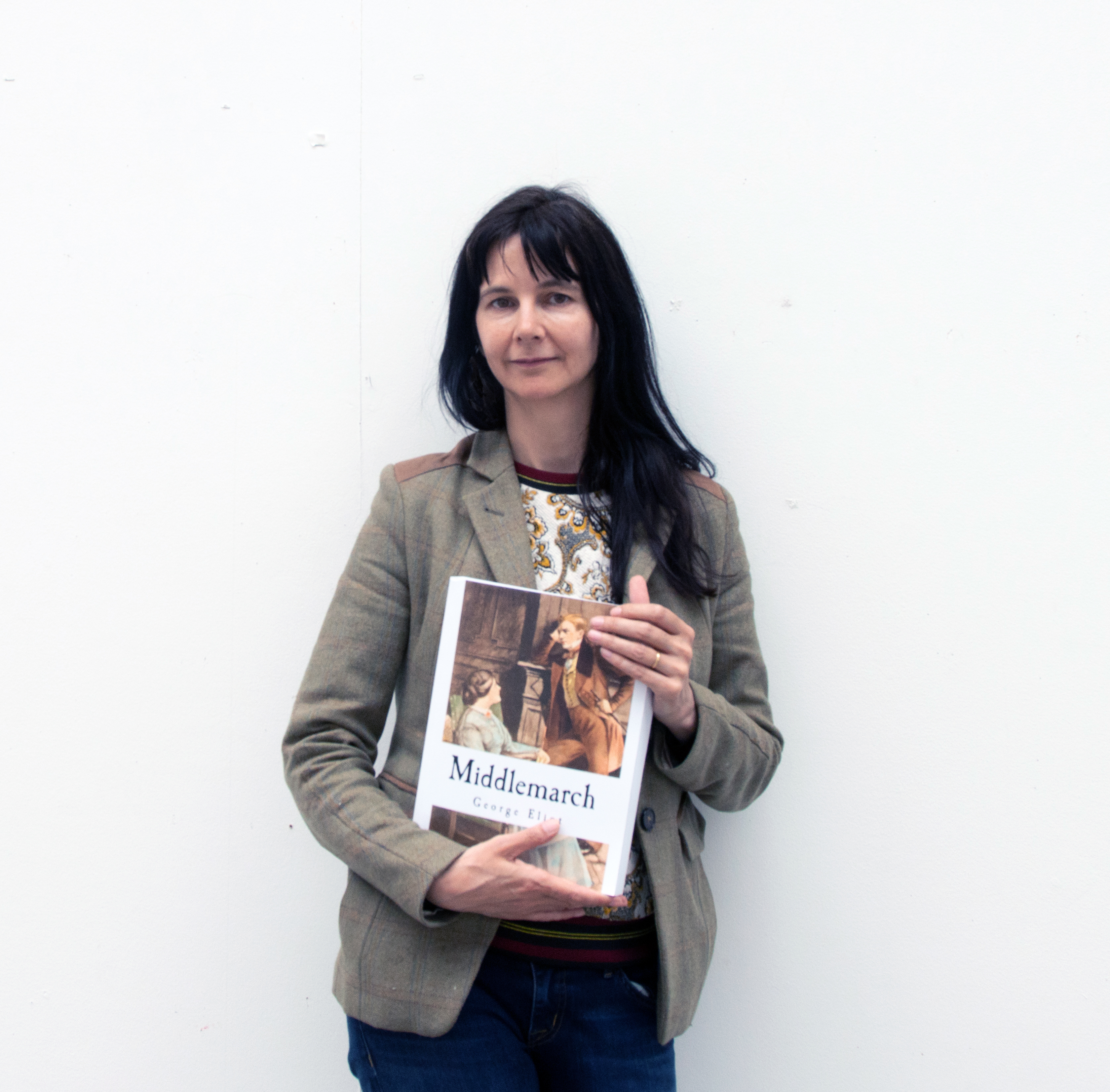 The artist Gillian Wearing stands holding a copy of Middlemarch by George Eliot