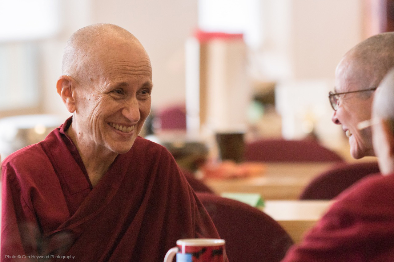 A photograph of Thubten Chodron dressed in a red robe, talking to other Buddhist nuns