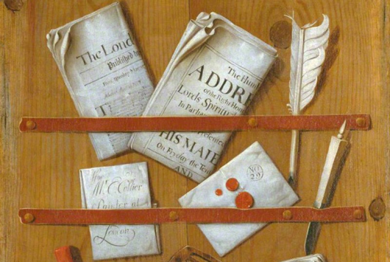 Letter, newspaper, envelopes and quills on a desk.