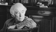 A black and white photograph of Seamus Heaney surrounded by book shelves, from the cover of a collection called 100 Poems