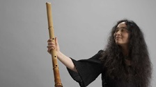 Kiku Day holds a shakuhachi flute up to the camera