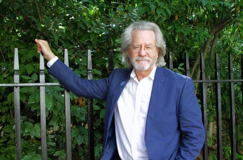 A C Grayling holding on to some metal railings.