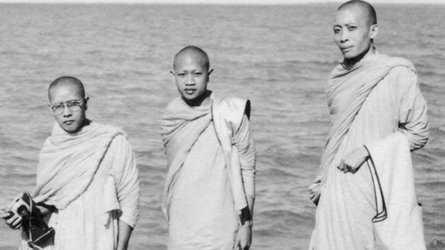 Three Buddhist monks standing on a rock by the sea.