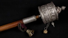 An old silver prayer wheel, with a long wooden handle and brass bell.