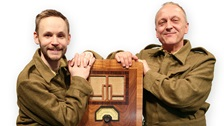 Two men dressed as characters from Dad's Army stand on either side of a radio