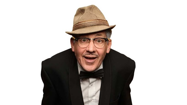 Count Arthur Strong smiles into the camera wearing a hat, glasses and a bowtie