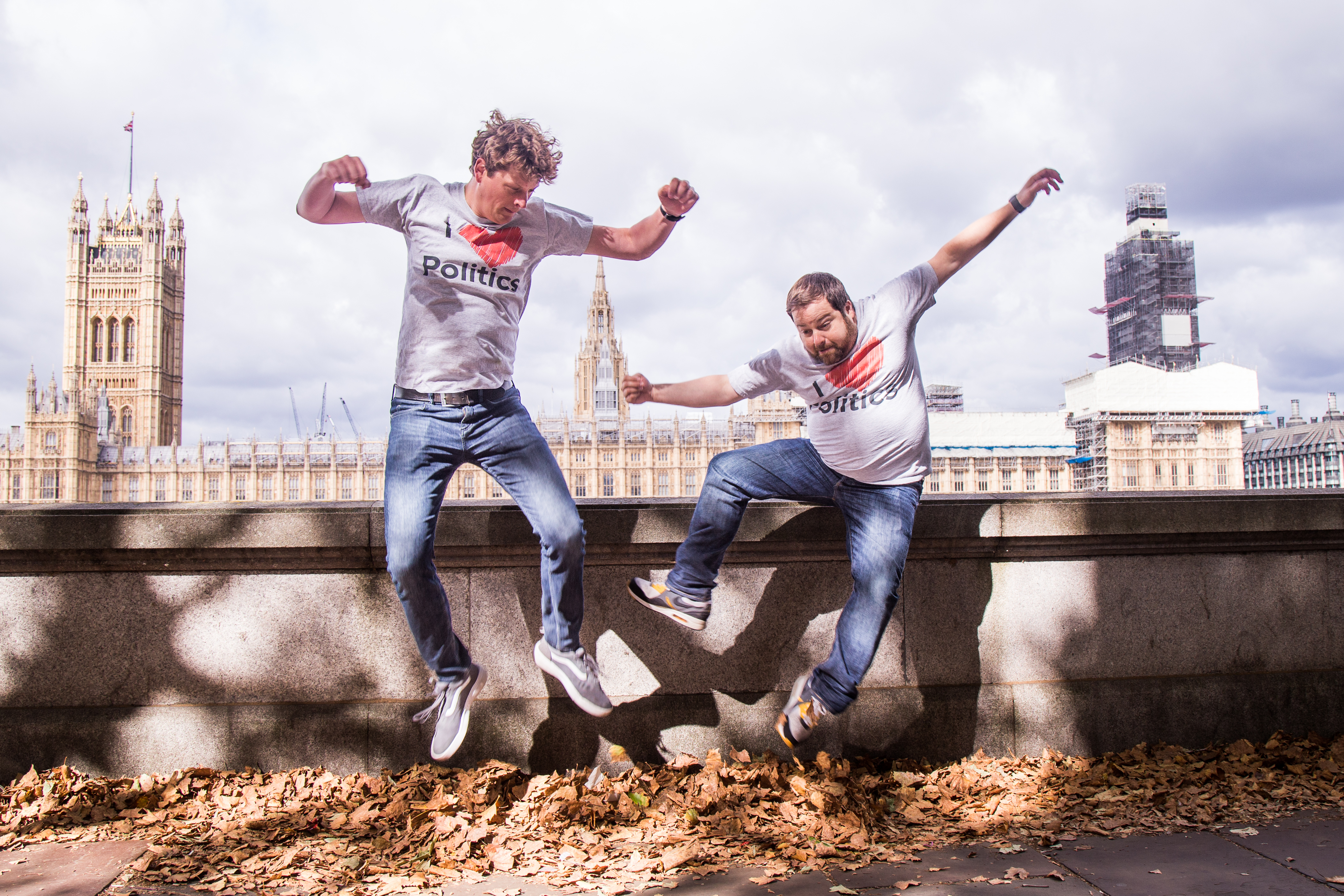 Photograph of two male comedians leaping off a ledge near the Thames with Westminster in the background