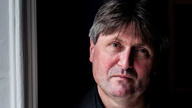 A photograph of Simon Armitage standing in a doorway