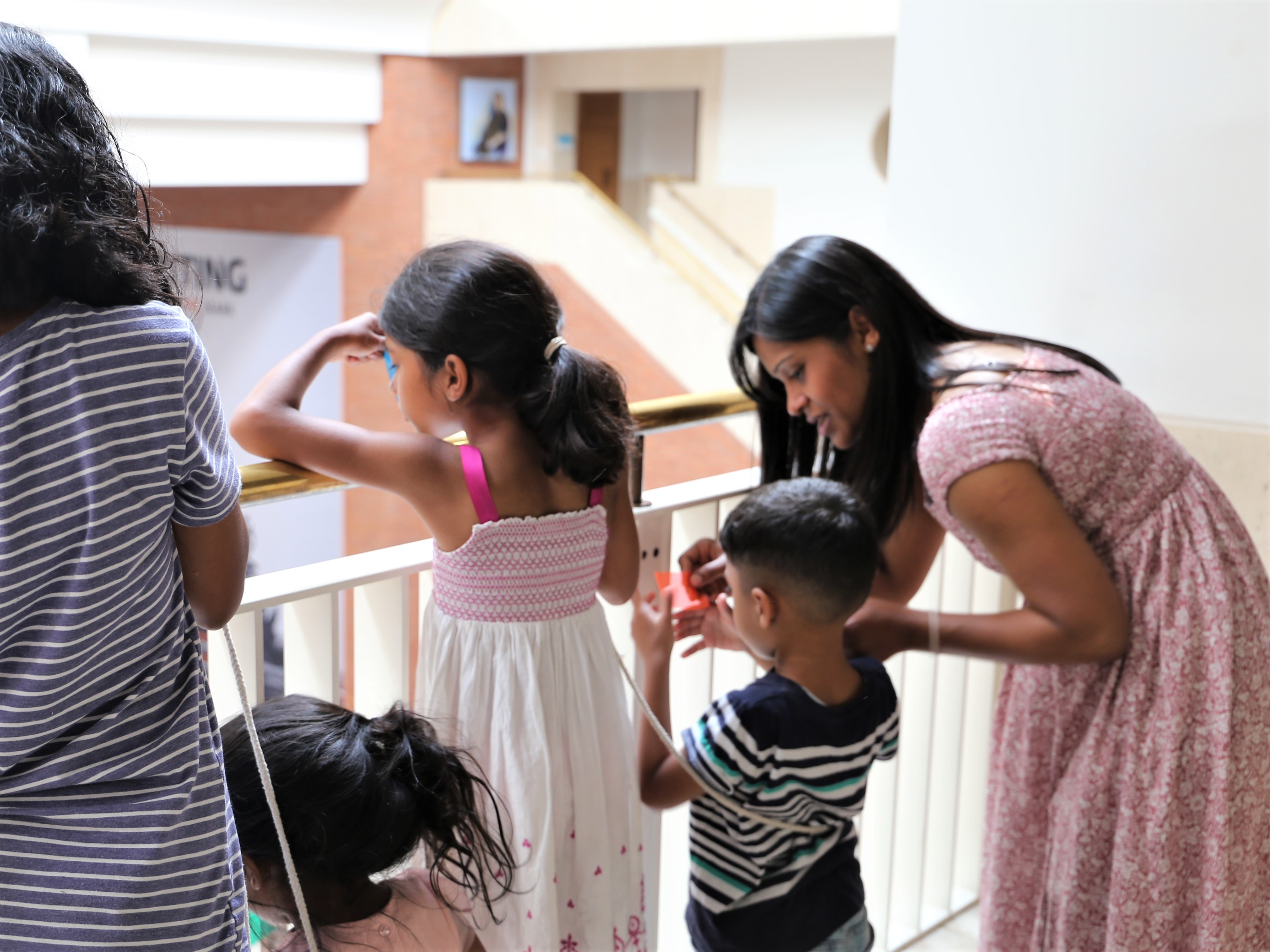 A family look over a balcony at the British Library