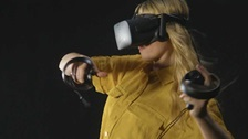 A woman wearing virtual reality goggles engaged in a virtual reality activity.