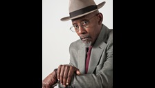 Linton Kwesi Johnson in a suit and hat