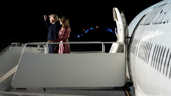 President Donald J. Trump, joined by First Lady Melania Trump, waves to members of the press as they disembark Air Force One at night (Official White House Photo)