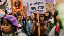Feminists demonstrating and holding placards.