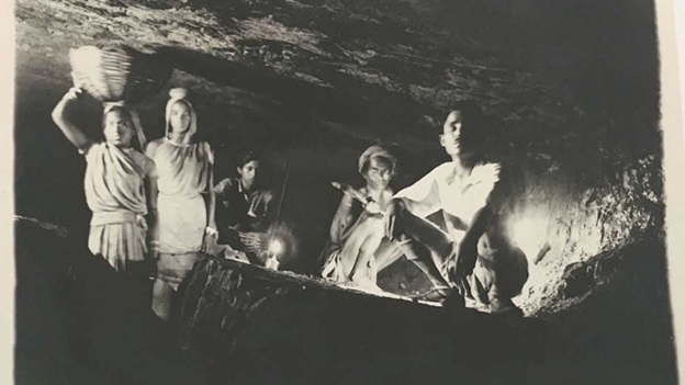 Photograph inside an Indian mine, with two women walking in a trench and three men crouching.