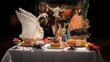 A peacock, swan and other birds on dishes on a table.