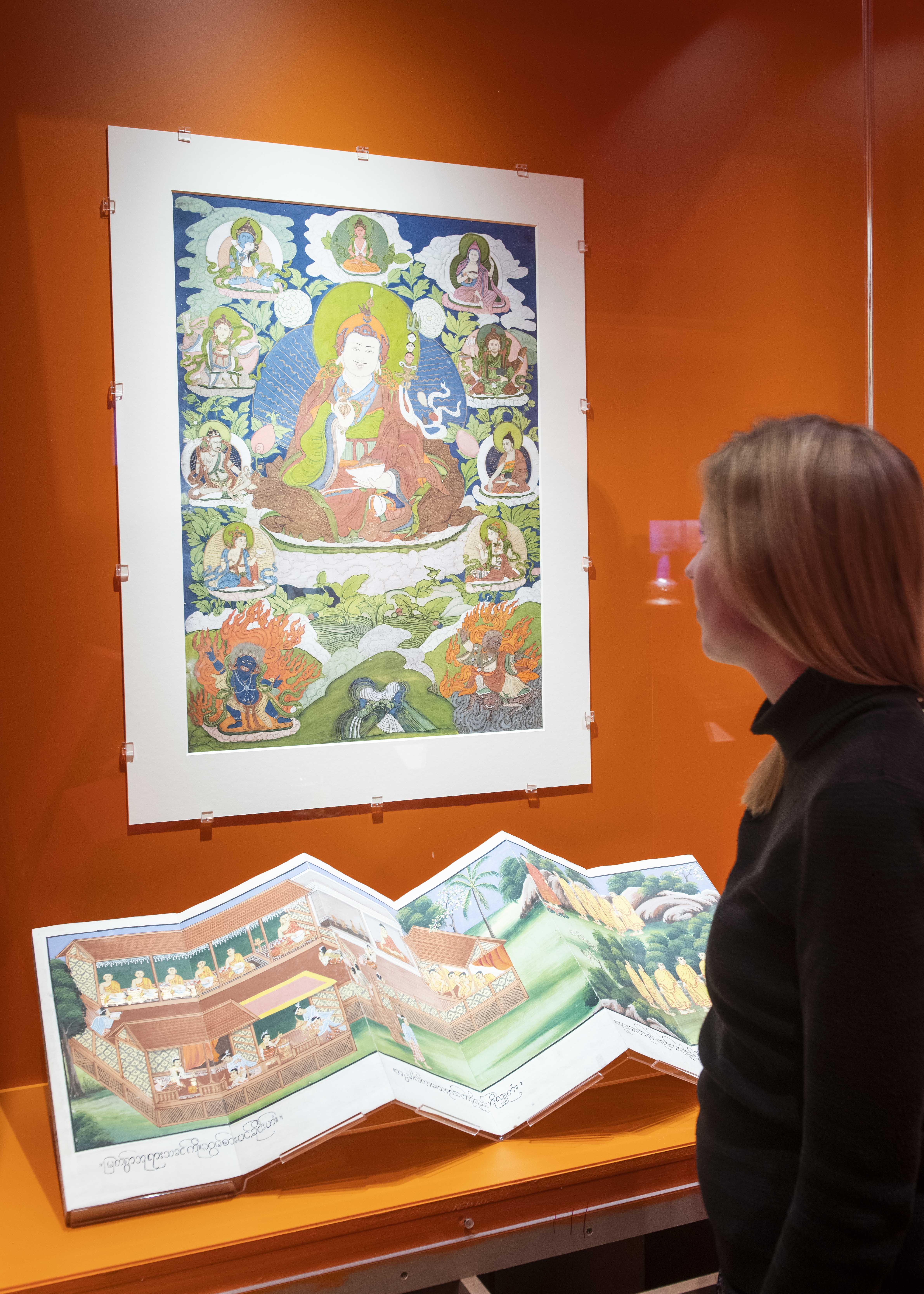 Visitor looking at Buddhist manuscript