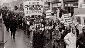 Photograph of crowds marching with feminist banners at a Women's Liberation demonstration