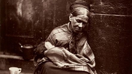 19th century photograph of a woman sat leaning against a street wall, holding a baby