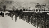 Photograph of World War One soldiers lined up in rows, with snowy mountains in background