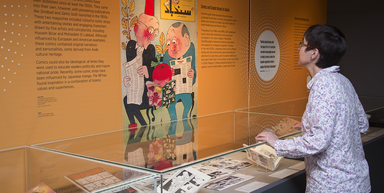 Exhibition visitor looking at the Arabic Comics display