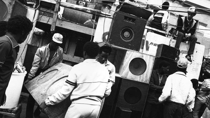 Black and white photograph showing group at Notting Hill carnival installing a sound system