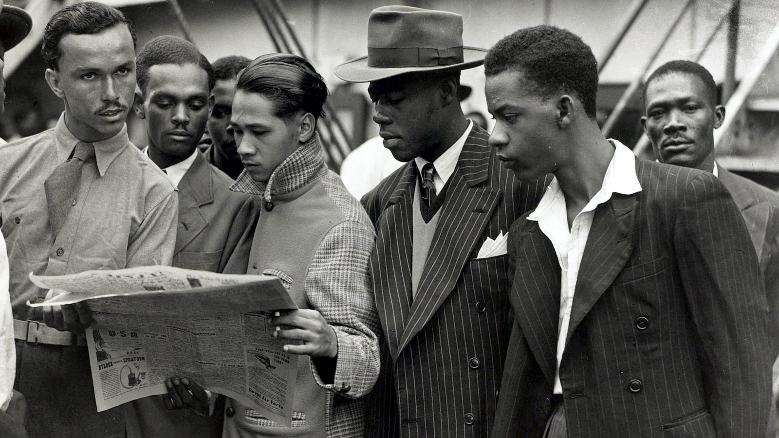 Banner showing 5 men reading a newspaper in 1948