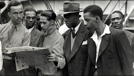 Black and white photograph of a group of Caribbean men reading a newspaper at Tilbury docks, June 1948