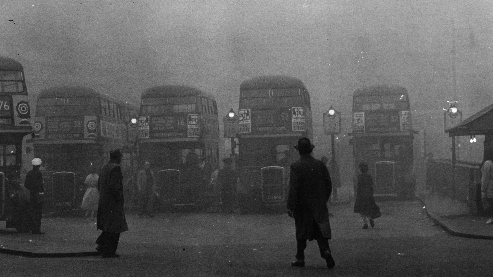 Black and white photograph of London buses in the smog, c. 1960