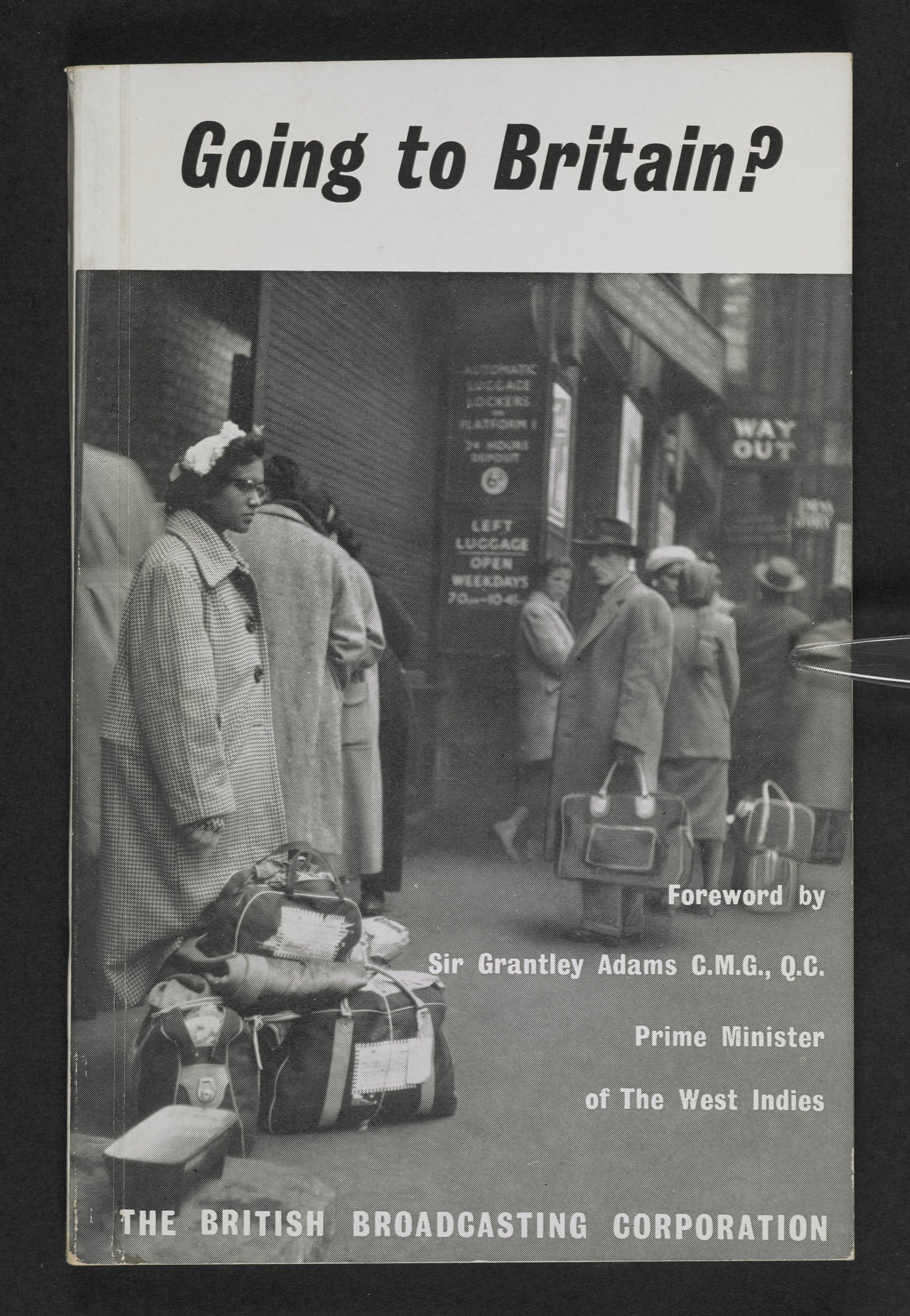 Front cover for the BBC pamphlet, Going To Britain?, featuring a photograph of a Caribbean woman in a coat standing with luggage next to a train station exit