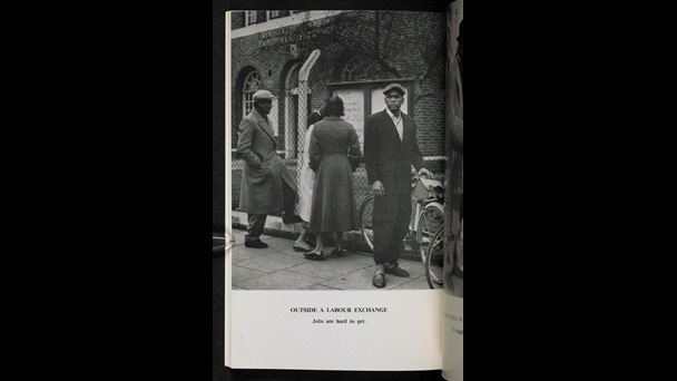 Black and white photograph titled 'Outside the labour exchange. Jobs are hard to get', showing a group of people. From the BBC pamphlet, Going To Britain?