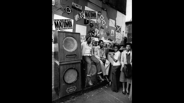Photograph taken by Adrian Boot showing people sitting on a sound system on Portobello Road, Notting Hill Carnival 1979