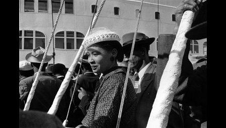 Black and white photograph of an unnamed Caribbean woman leaving a ship which had recently landed in Southampton Docks, May 1956