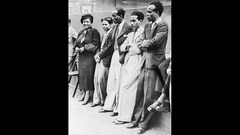 Black and white photograph of Amy Jacques Garvey and four men including the sons of the Ethiopian minister, standing against a wall at a International African Friends of Abyssinia demonstration in Trafalgar Square